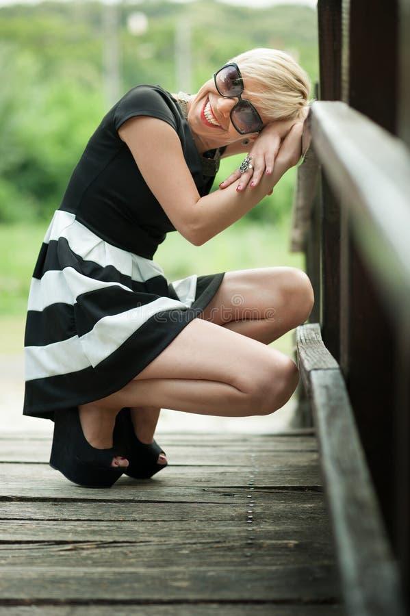 Louro atrativo na ponte de madeira que agacha-se imagens de stock royalty free