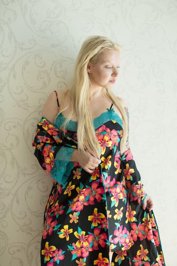 Louro atrativo novo em uma camiseta brilhante e em uma veste brilhante com teste padrão de flor fotos de stock