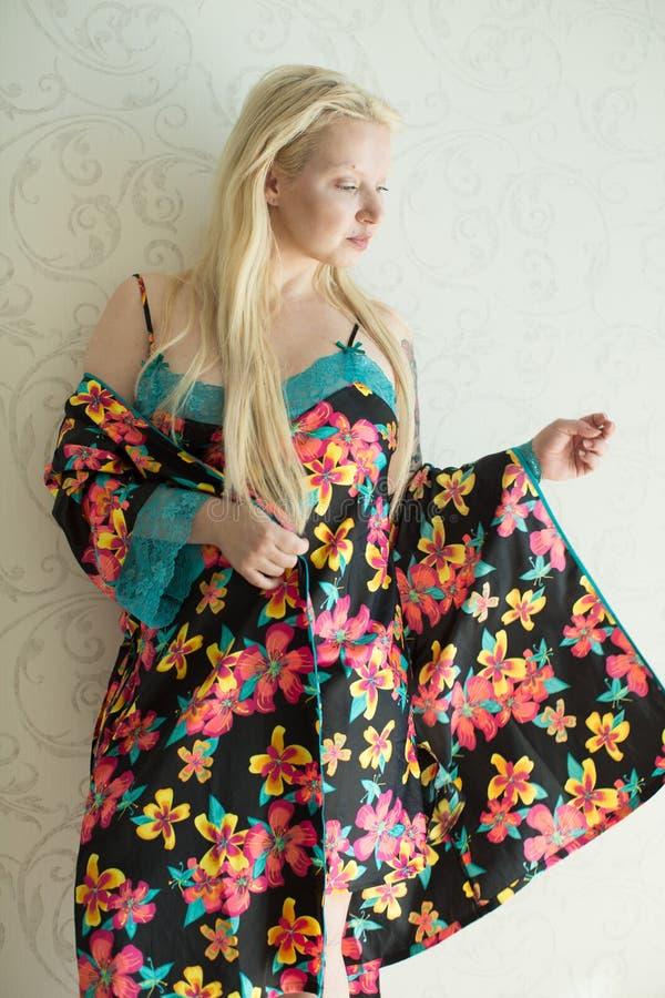 Louro atrativo novo em uma camiseta brilhante e em uma veste brilhante com teste padrão de flor fotografia de stock