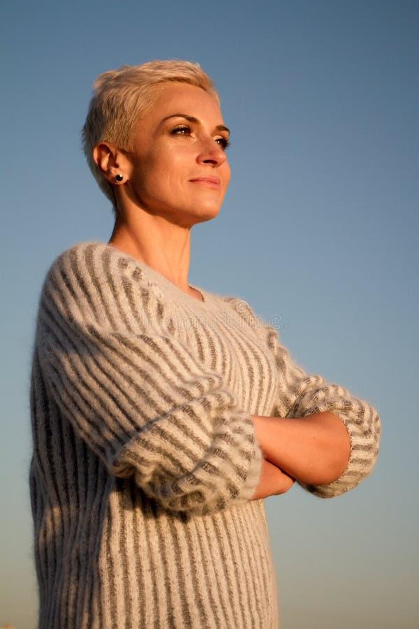 Louro bonito da jovem mulher com um corte de cabelo curto no short e em uma camisa branca que olha o mar fotos de stock royalty free