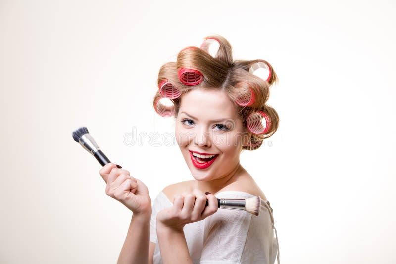 Louro bonito de sorriso com escovas foto de stock