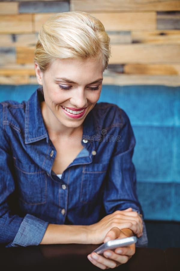 Louro bonito de sorriso que envia uma mensagem de texto foto de stock