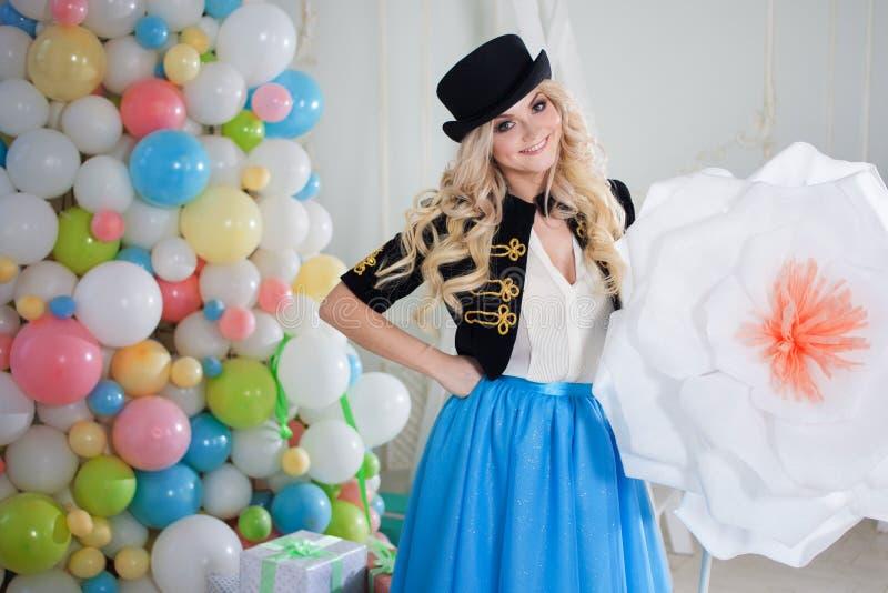 Louro bonito e bonito com a flor enorme surpreendente Jovem mulher encantador em uma saia azul curvy fotos de stock royalty free