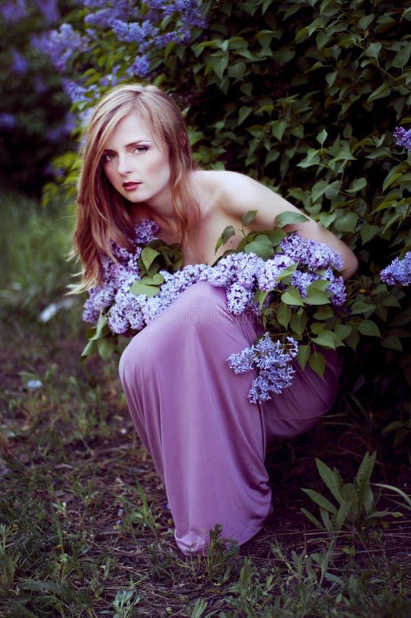 Louro bonito em arbustos lilás fotografia de stock royalty free