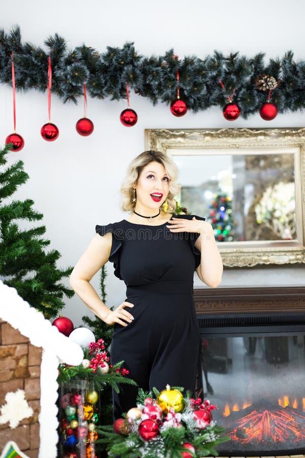 Louro bonito em um vestido preto no cenário de ano novo em um estúdio da foto imagem de stock