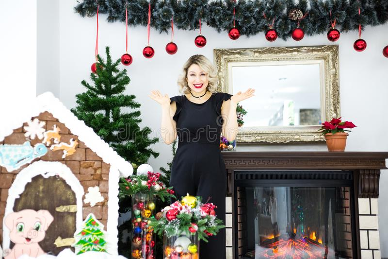 Louro bonito em um vestido preto no cenário de ano novo em um estúdio da foto imagem de stock royalty free