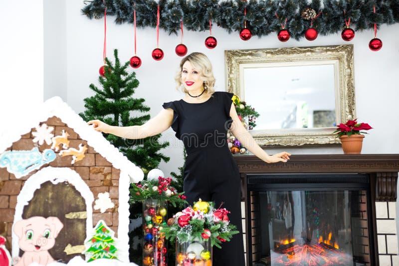 Louro bonito em um vestido preto no cenário de ano novo em um estúdio da foto fotos de stock