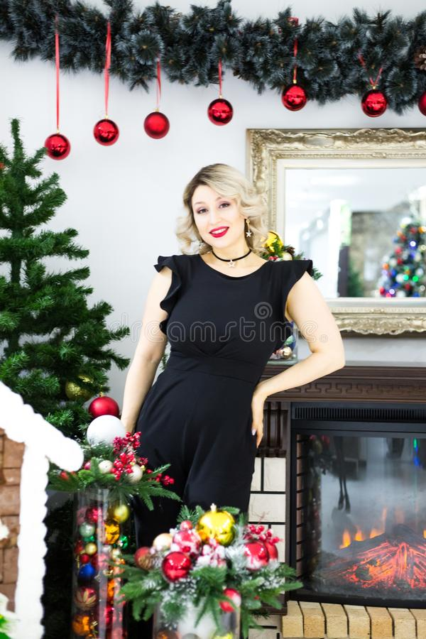 Louro bonito em um vestido preto no cenário de ano novo em um estúdio da foto foto de stock royalty free