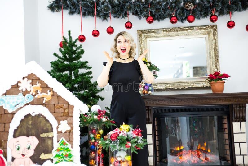 Louro bonito em um vestido preto no cenário de ano novo em um estúdio da foto fotografia de stock royalty free