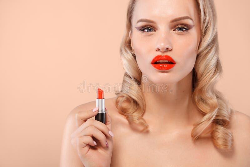 Louro bonito em uma maneira de Hollywood com ondas, bordos vermelhos, batom à disposição Face e cabelo da beleza imagem de stock