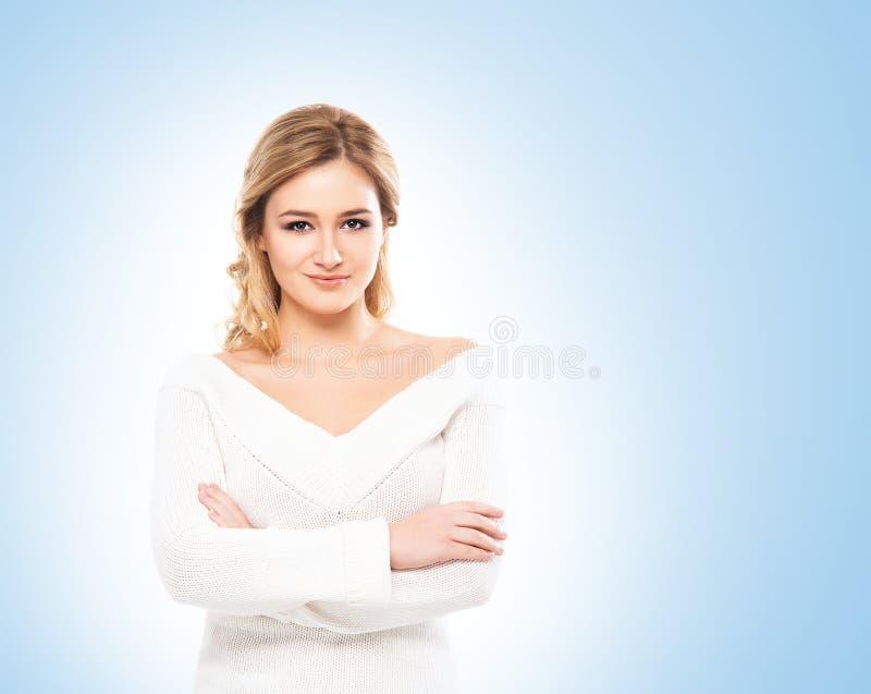 Louro bonito na malhas branca no fundo azul imagem de stock royalty free