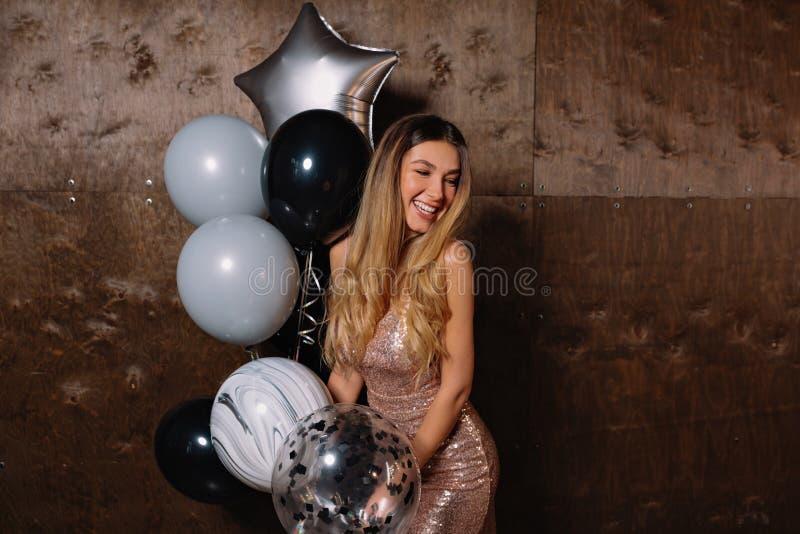 Louro bonito bonito no vestido de nivelamento sparkly que levanta com sorriso feliz à câmera com balões e que prepearing para a f foto de stock