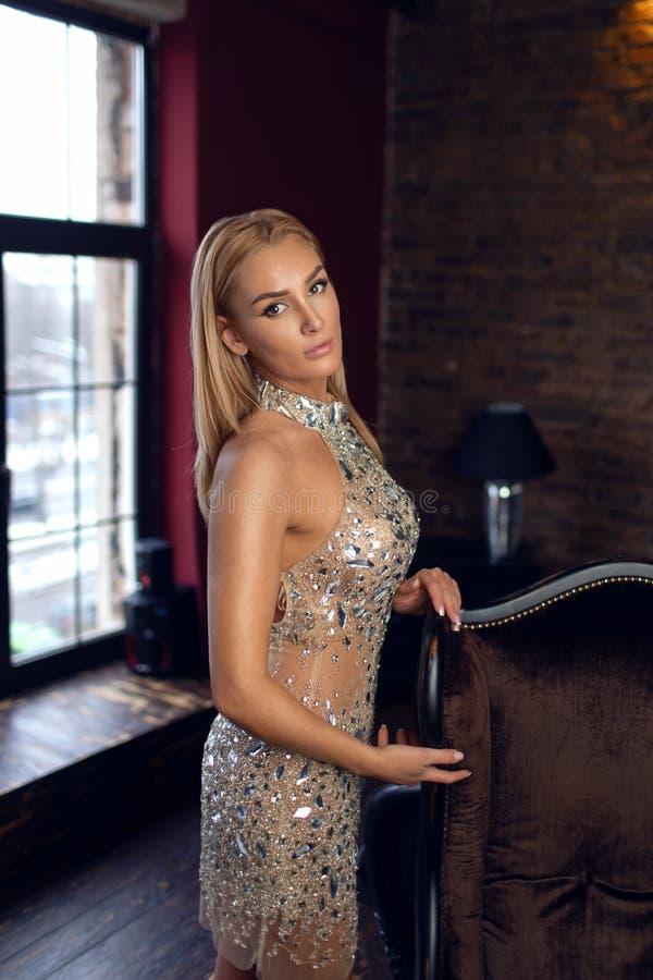 Louro bonito novo em um vestido de nivelamento lindo que levanta no interior imagens de stock royalty free