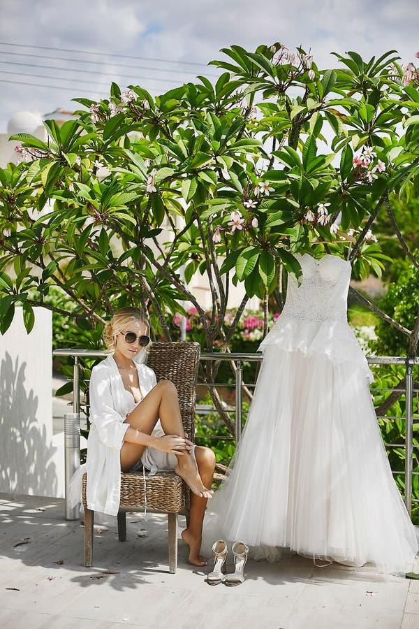 Louro bonito, pechugón e elegante, menina modelo com corpo 'sexy' no peignoir branco e na roupa interior, em à moda fotografia de stock