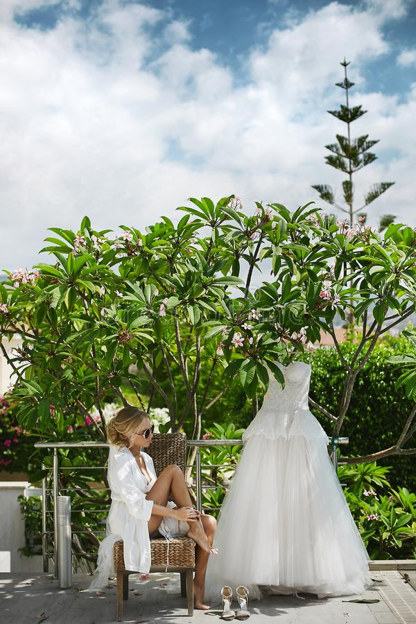 Louro bonito, pechugón e elegante, menina modelo com corpo 'sexy' no peignoir branco e na roupa interior, em à moda imagem de stock