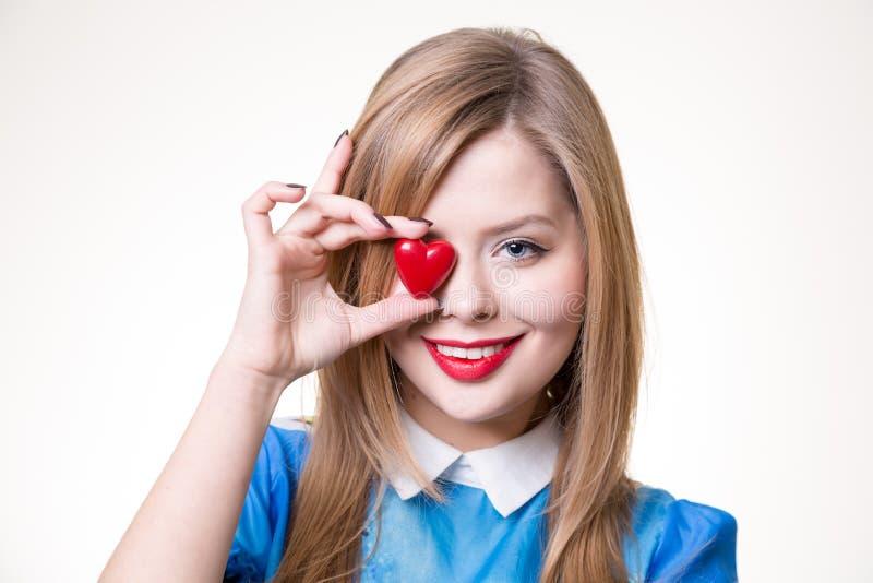 Louro bonito que guarda o coração vermelho foto de stock
