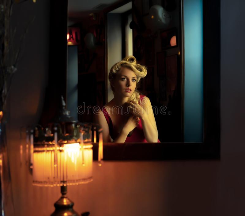 Louro bonito que olha si mesma em um espelho fotos de stock