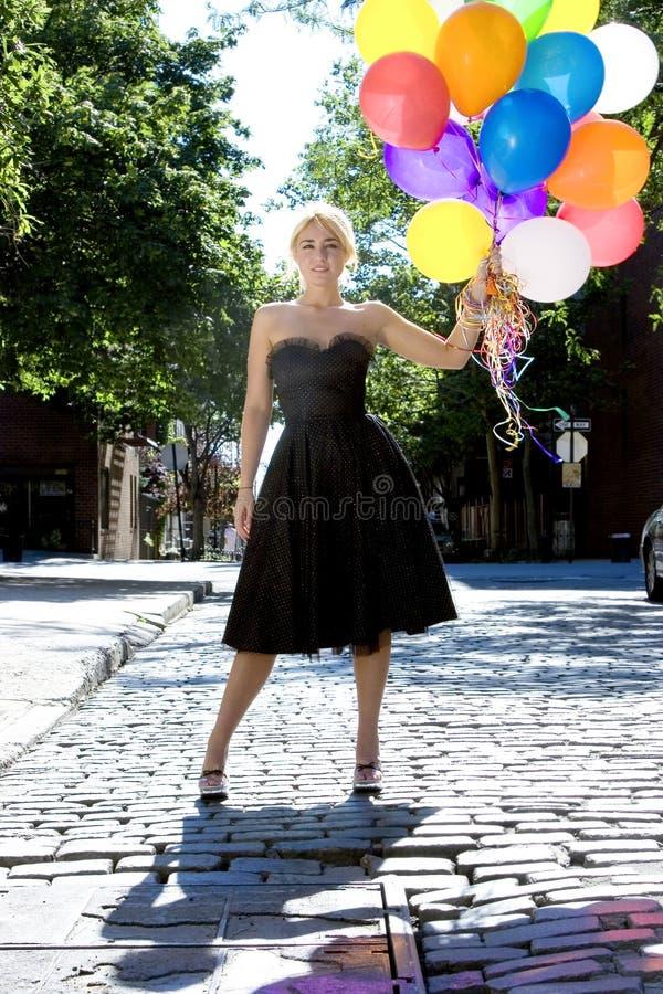 Louro com balões para fora no sol imagem de stock