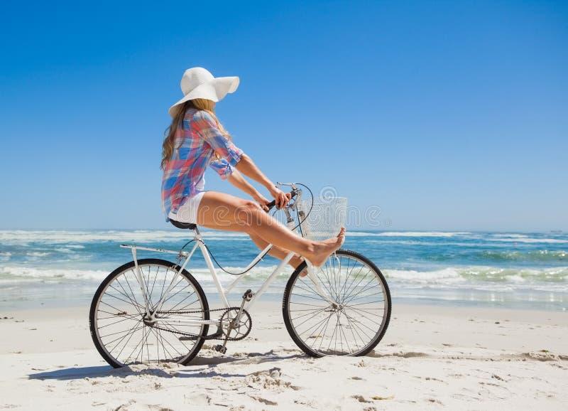 Louro consideravelmente despreocupado em um passeio da bicicleta na praia imagens de stock
