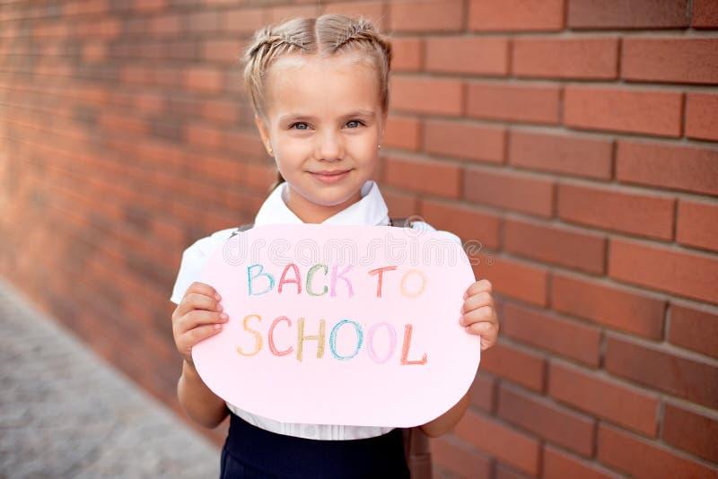 Louro da menina em suportes da farda da escola perto de uma parede de tijolo que guarda um quadro-negro com o texto de volta à e imagens de stock royalty free