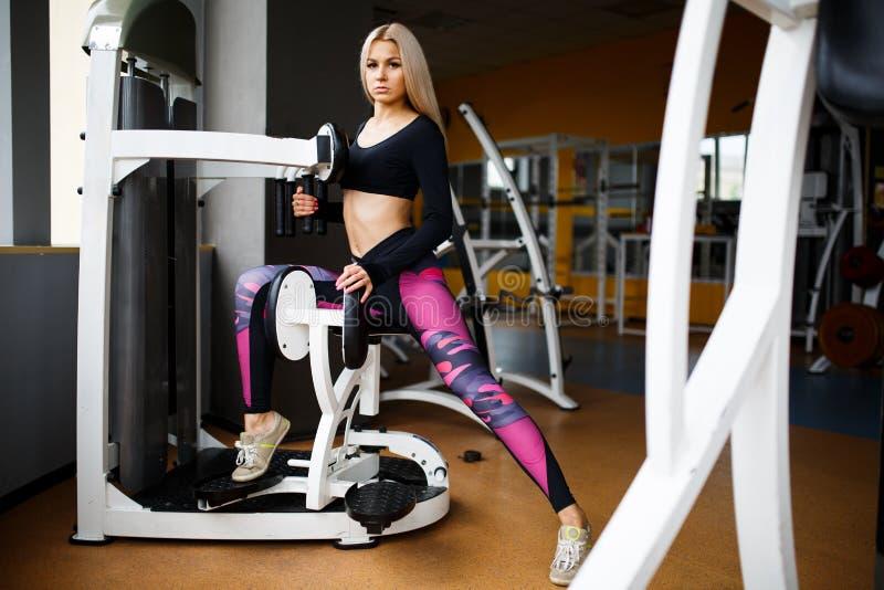 Louro da menina que faz exercícios no gym conceito de um estilo de vida saudável foto de stock
