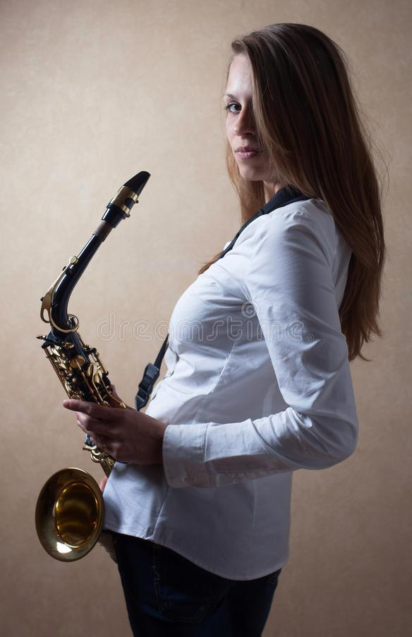 Louro de cabelos compridos bonito novo com saxofone fotografia de stock royalty free