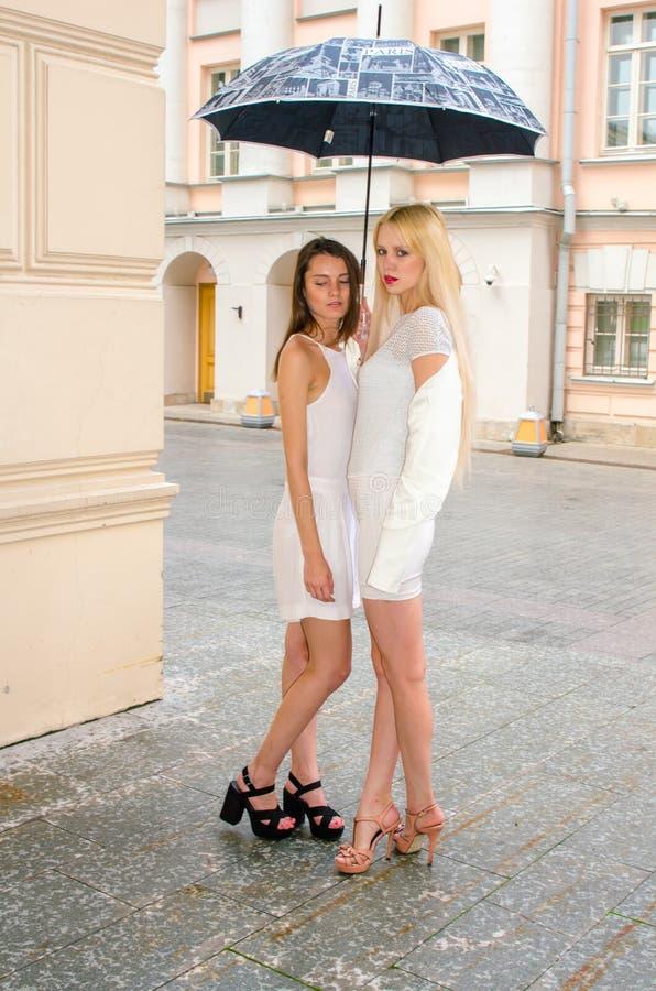 Louro de dois amigos e moreno nos vestidos brancos que escondem do tempo sob um grande guarda-chuva nas aleias da cidade velha imagens de stock
