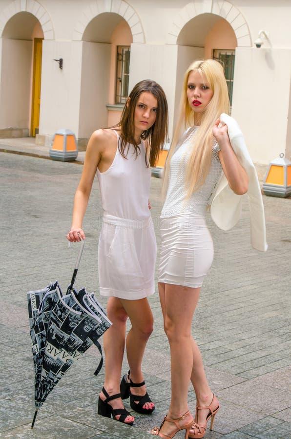 Louro de dois amigos e moreno nos vestidos brancos que escondem do tempo sob um grande guarda-chuva nas aleias da cidade velha foto de stock royalty free