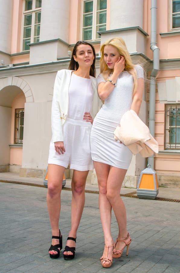 Louro de dois amigos e moreno nos vestidos brancos que levantam na rua da cidade velha imagem de stock