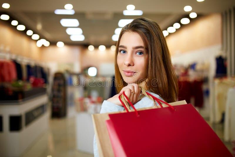 Louro de sorriso atrativo na compra na alameda Menina caucasiano bonita que guarda sacos de compras do colorfull com copyspace de fotos de stock