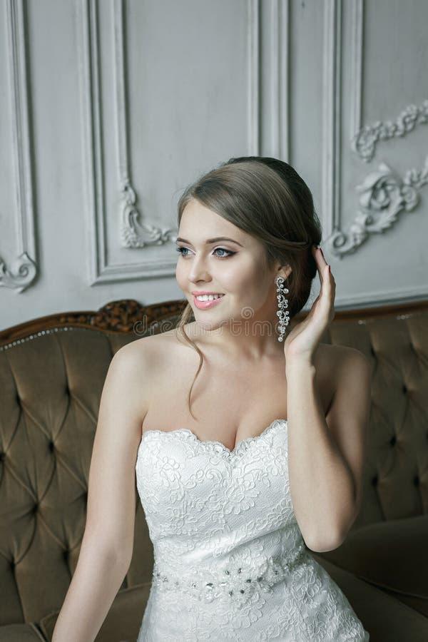 Louro de sorriso feliz da noiva no vestido de casamento Interior luxuoso imagem de stock