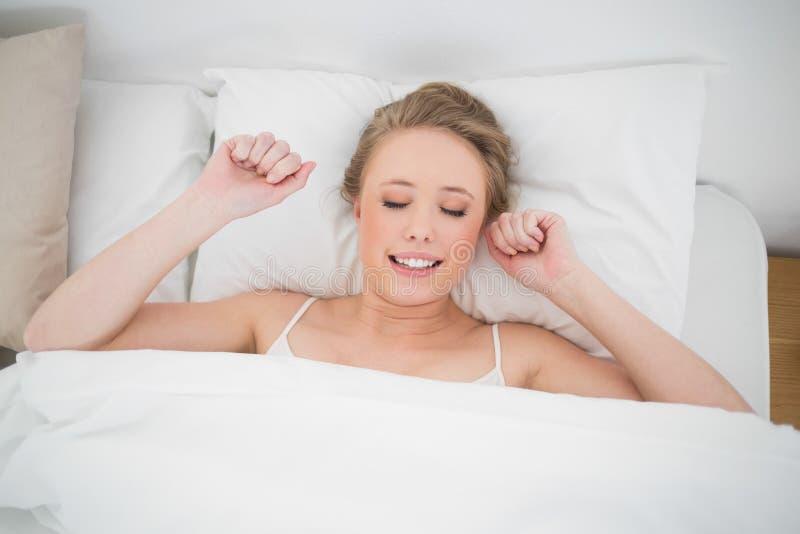 Louro de sorriso natural que encontra-se na cama com olhos fechados foto de stock