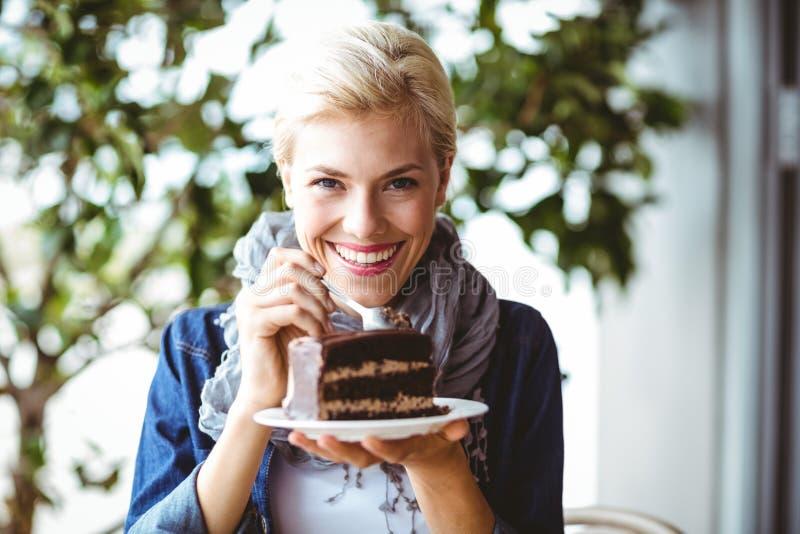 Louro de sorriso que toma uma parte de bolo de chocolate fotos de stock
