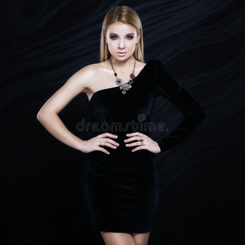 Louro elegante bonito em um vestido preto imagem de stock royalty free