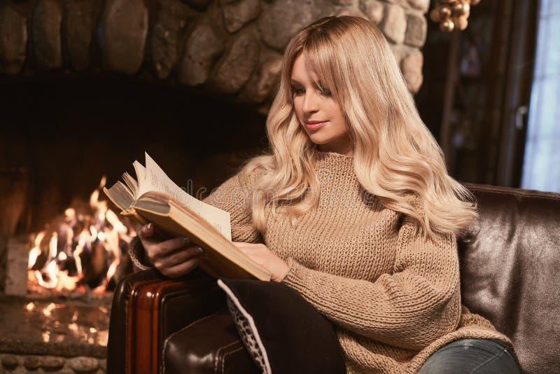 Louro elegante de Georgeous com o livro perto da chaminé foto de stock
