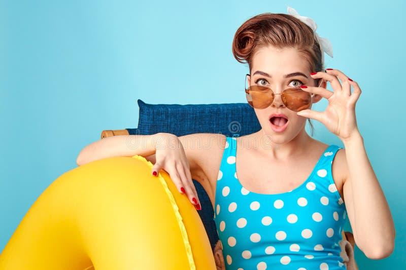 Louro em um maiô e nos vidros que sentam-se em uma cadeira de plataforma com um círculo inflável imagens de stock