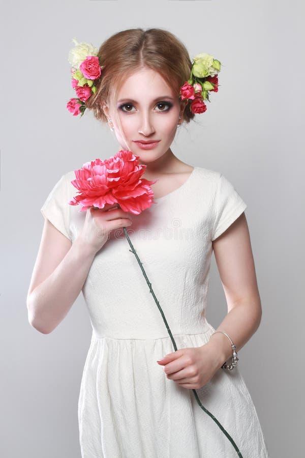 Louro encantador com as flores em seu cabelo e em suas mãos Brigh foto de stock royalty free