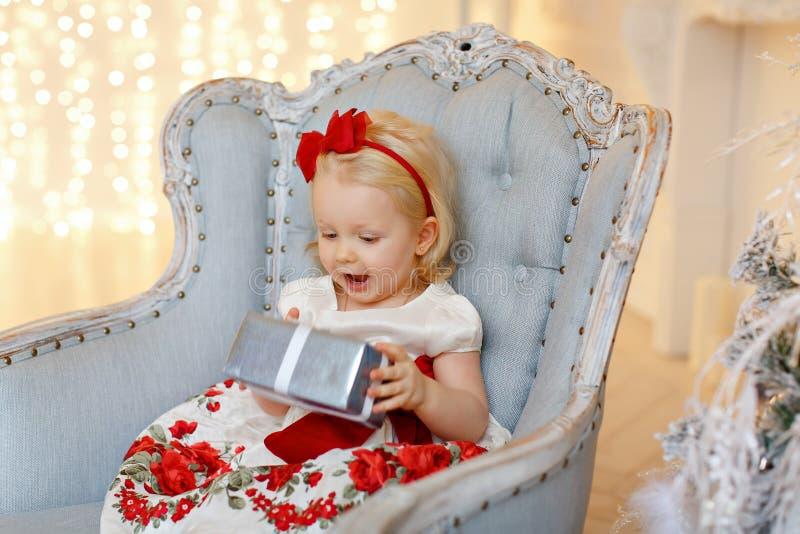 Louro encantador do bebê pequeno em um vestido vermelho que senta-se em um cha foto de stock royalty free
