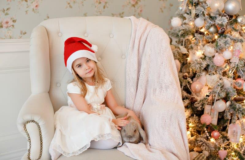 Louro encantador muito agradável da menina no vestido branco e Santa h fotos de stock
