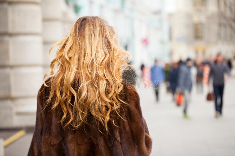 Louro encaracolado na rua de passeio do outono do casaco de pele Cabelo ondulado saudável Vista traseira imagens de stock royalty free