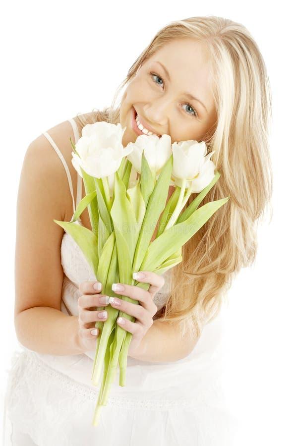 Louro feliz com tulips brancos imagem de stock royalty free