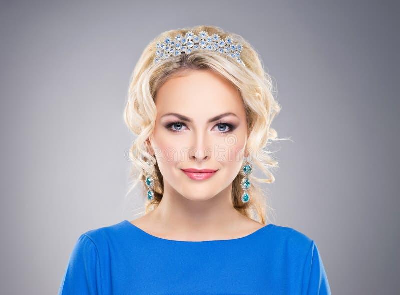 Louro lindo, novo vestindo uma coroa e brincos da safira foto de stock
