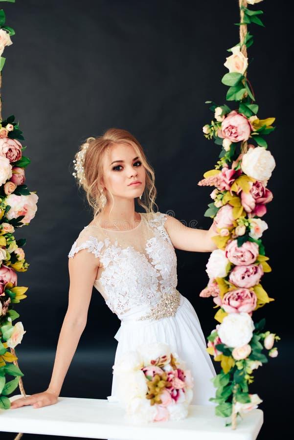 Louro muito bonito com olhos azuis no vestido branco uma noiva em um balanço no estúdio em um fundo preto fotografia de stock royalty free