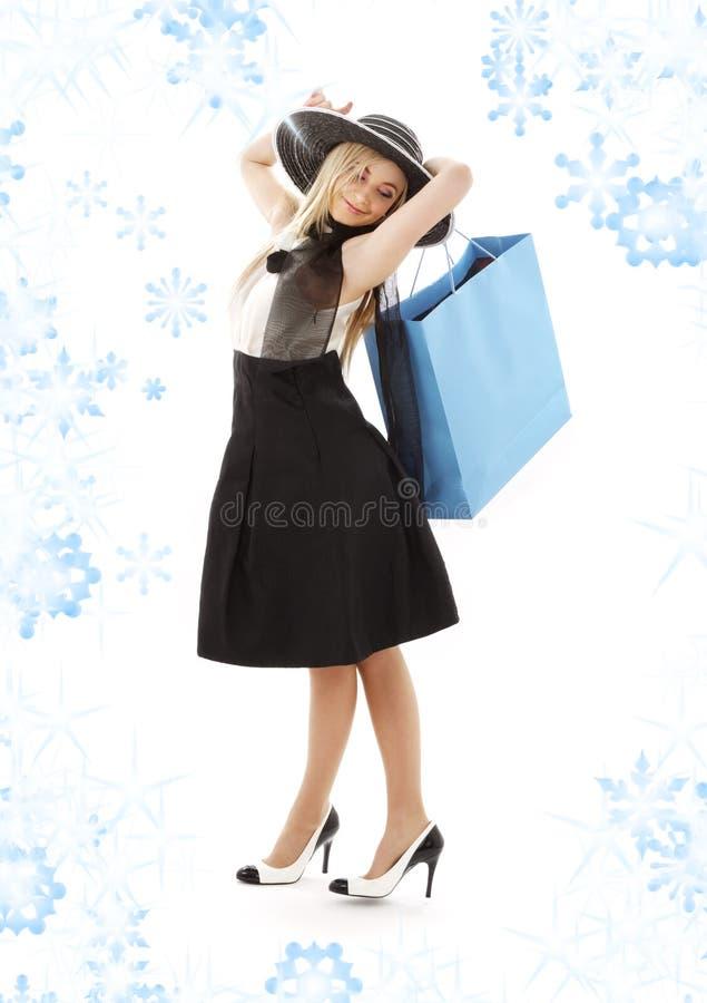 Louro no chapéu retro com o saco de compra azul fotos de stock