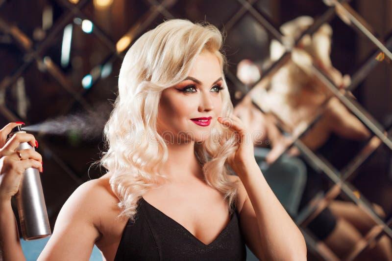 Louro novo bonito que faz seu cabelo Composição glamoroso a jovem mulher atrativa usa a laca fotografia de stock