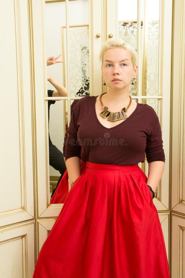Louro novo em uma camiseta vermelha, em uma saia de Borgonha e em uns ornamento étnicos ao lado de um espelho imagens de stock royalty free
