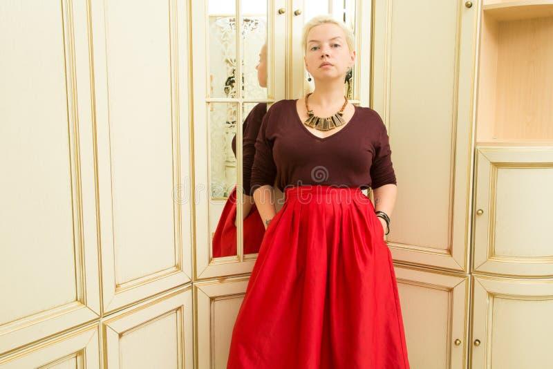 Louro novo em uma camiseta vermelha, em uma saia de Borgonha e em uns ornamento étnicos ao lado de um espelho fotos de stock