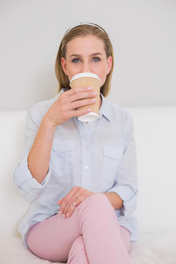Louro ocasional satisfeito que senta-se no sofá que bebe do copo descartável foto de stock