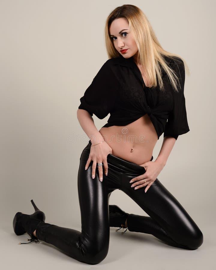 Louro pernudo delgado da menina em caneleiras pretas e em uma camisa em seus joelhos fotografia de stock royalty free