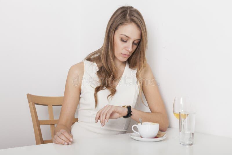 Louro que agita seu café que olha o telefone celular fotografia de stock